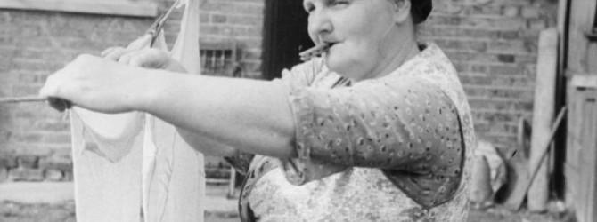 Eine Hausfrau mit einer Wäscheklammer zwischen den Lippen hängt ein weißes Stück Wäsche zum Trocknen auf.