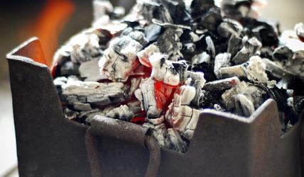 Ein Aschekasen aus Metall mit noch frischer, heißer Glut und Aschestücken darin