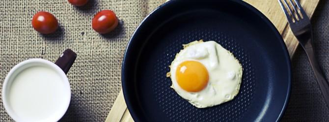 Ein Spiegelei liegt in einer runden Bratpfanne, die auf einem Brett steht. Daneben liegen Tomaten, eine Scheibe Brot und eine Tasse Kaffee.